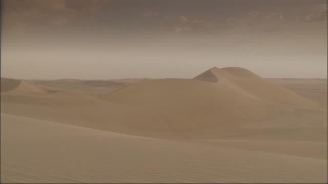 vídeos de stock, filmes e b-roll de long shot, pan-right - the sun sets over a stretch of barren egyptian desert / egypt - duna