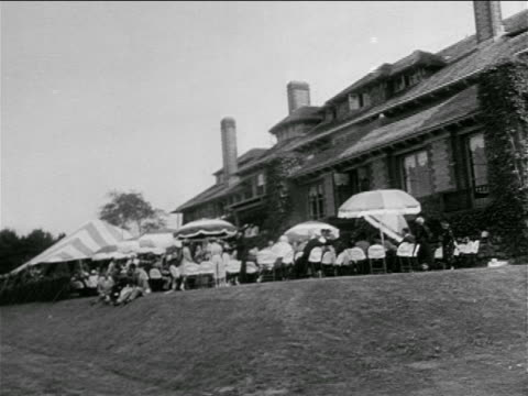 b/w 1953 long shot people at umbrella tables outside of mansion / kennedy/bouvier wedding reception - john f. kennedy us president stock videos and b-roll footage