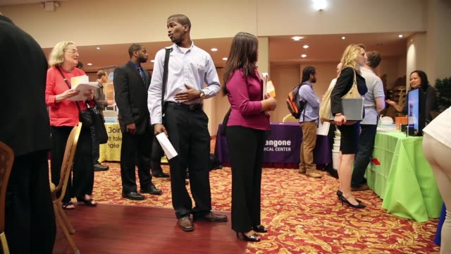 long shot people queueing job seekers meet potential employers at a job fair held in a conference room of the holiday inn in midtown manhattan - unemployment queue stock videos & royalty-free footage