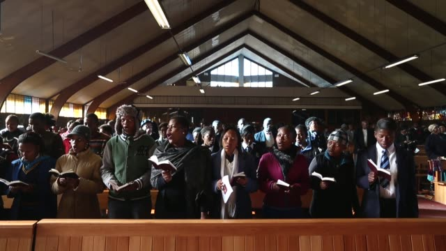 long shot people singing at church the congregation prays during a sunday service at regina mundi church in soweto on june 16 2013 in johannesburg... - afrikaans stock videos & royalty-free footage