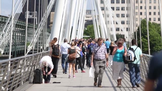 long shot, people walking across hungerford bridge. - hungerford bridge stock videos & royalty-free footage