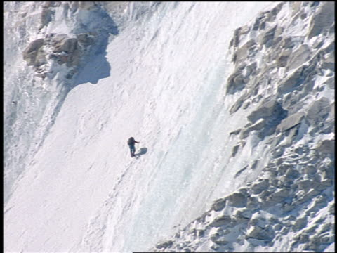 long shot person slowly climbing north face of mt everest / himalayas - mount everest stock-videos und b-roll-filmmaterial