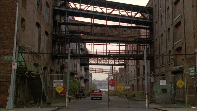 long shot pick-up truck riding down alley under catwalks between industrial buildings / new york city - anno 1994 video stock e b–roll