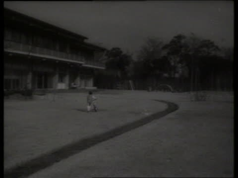 long shot prince hiro of japan with bicycle on palace grounds / 1960's / sound - solo bambini maschi video stock e b–roll