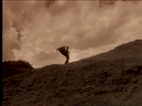 sepia long shot profile man carrying basket of hay walking up hill with walking stick - viraggio video stock e b–roll