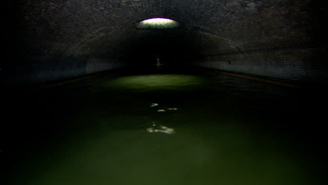 Long Shot push-in - Green water flows through a tunnel. / Paris, France