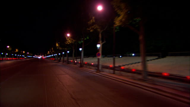 Long Shot push-in - Lampposts illuminate a Paris street at night. / Paris, France