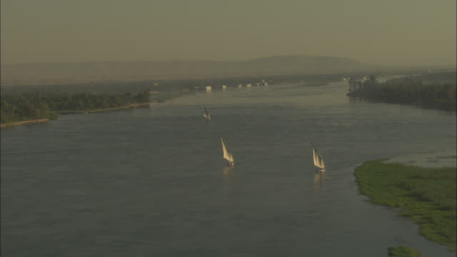 Long Shot, push-in - Sailboats travel along the Nile River / Egypt