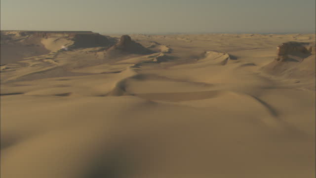 long shot, push-in tracking-right - dunes stretch over the vast desert landscape / egypt - terra brulla video stock e b–roll