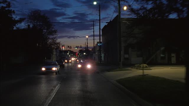 long shot rear car point of view traveling along small town main street at dusk / louisiana - louisiana stock videos & royalty-free footage