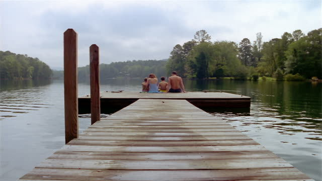 Long shot rear view of family sitting at end of dock on lake / putting arms around each other
