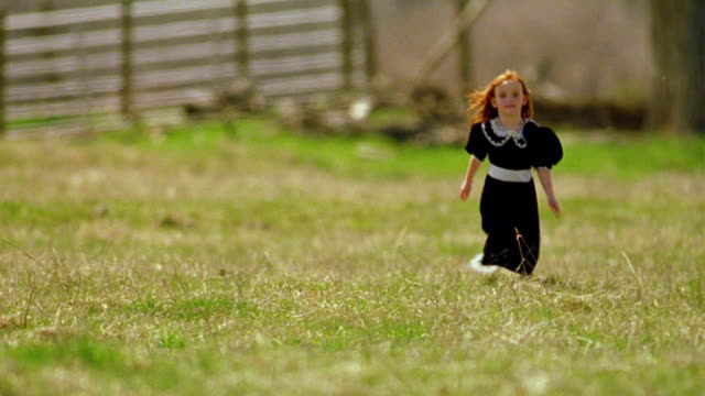 long shot redheaded girl in black dress running in green field toward camera / fence in background / montana - black dress stock videos & royalty-free footage