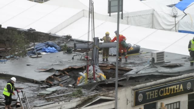 long shot rescuers lift the police helicopter wreckage from the roof of the the clutha pub on december 2 2013 in glasgow scotland a ninth body has... - ヘリコプター事故点の映像素材/bロール
