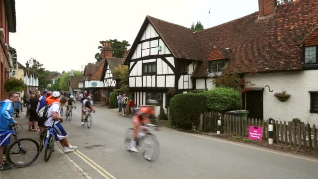 long shot riders pass through the small village of shere during stage seven of the tour of britain from epsom racecourse to guildford on september 21... - tour of britain stock videos & royalty-free footage
