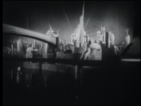 B/W 1940 long shot searchlights over futuristic city with bridge at night