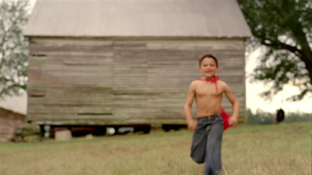 Long shot shirtless boy wearing a red cape running towards CAM / flexing muscles and making a face