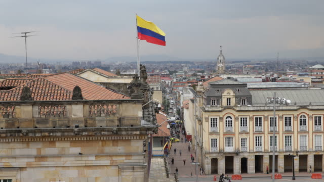 long shot, showing a view over the rooftop of the capitolio nacional and the surrounding cityscape a columbian flag can be seen. - bogota stock videos & royalty-free footage