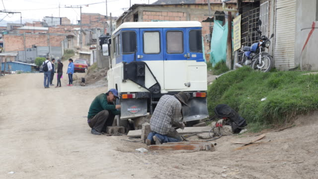 Long shot showing two men repairing a vehicle beside an unpaved road one man is welding something in the background are people and dogs on the road...