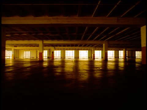 stockvideo's en b-roll-footage met sepia long shot silhouette black male athlete running past windows in large garage - parkeren