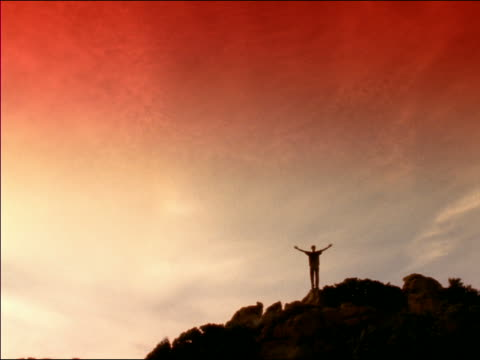long shot silhouette of young man standing on top of rocky hill raising arms in victory at sunset / corsica - menschliche gliedmaßen stock-videos und b-roll-filmmaterial