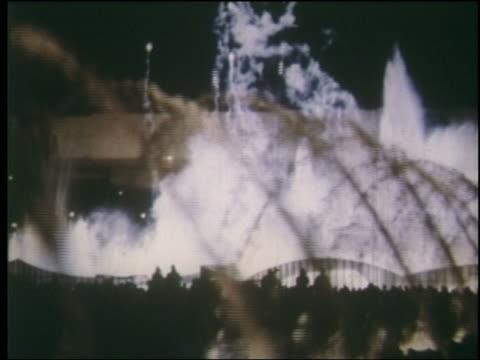 vidéos et rushes de 1964 long shot silhouetted people fireworks smoke with fountains in foreground at night / ny world's fair - exposition universelle de new york