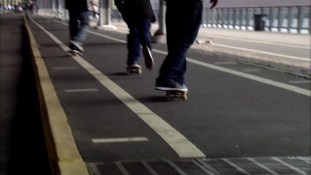 long shot skateboarders performing tricks under fdr drive / new york city - skateboarding stock videos & royalty-free footage