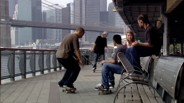 Long shot skateboarders skating near East River under FDR drive / talking to woman on bench / NYC