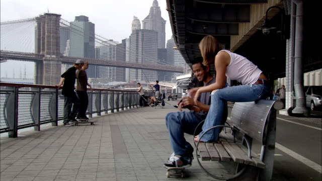 Long shot skateboarders under FDR Drive near East River / boy sitting and talking to girl / New York City