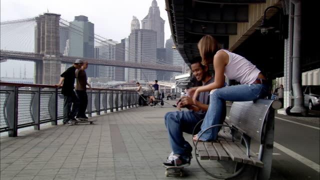stockvideo's en b-roll-footage met long shot skateboarders under fdr drive near east river / boy sitting and talking to girl / new york city - voetgangerspad
