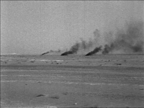 b/w 1967 long shot smoke rising after 3 explosions in desert in six day war / newsreel - sechstagekrieg stock-videos und b-roll-filmmaterial