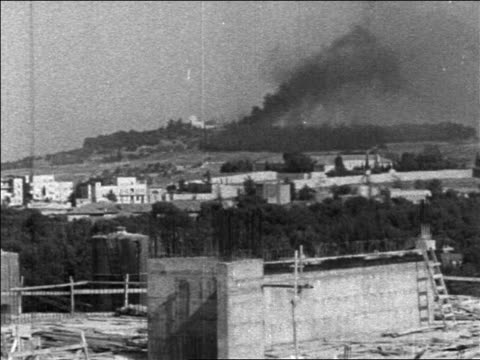 b/w 1967 long shot smoke rising after bombing in six day war / jerusalem / newsreel - sechstagekrieg stock-videos und b-roll-filmmaterial