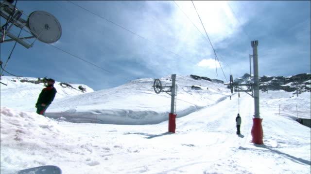 long shot snowboarders riding button ski lift up mountainside / morzine, france - ski lift stock videos & royalty-free footage