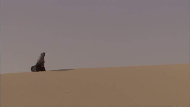 Long Shot, static - A Bedouin woman sits near the top of a sand dune / Egypt