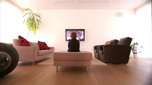 long shot static - a boy sits on an ottoman and watches television.   - guardare la tv video stock e b–roll