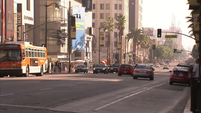long shot static - a city bus passes kodak theatre on hollywood boulevard. / los angeles, california, usa - establishing shot stock videos & royalty-free footage