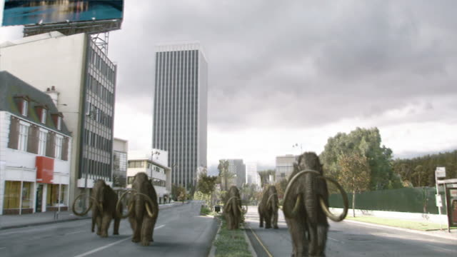 Long Shot static - A city crumbles around a herd of mastodons in a computer-generated animation. / Los Angeles, California, USA