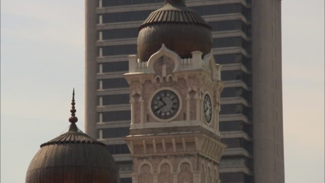 long shot static - a clock keeps time in a domed tower in malaysia. / kuala lumpur, malaysia - clock tower stock videos & royalty-free footage