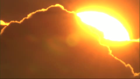 long shot static - a cloud with a golden outline drifts in front of the sun. / hawaii, usa - sunset stock videos & royalty-free footage