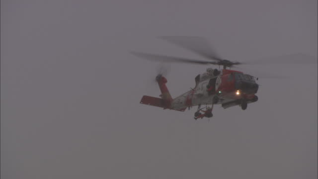 Long Shot static - A Coast Guard helicopter moves slowly as it uses a hoist to retrieve a crew member
