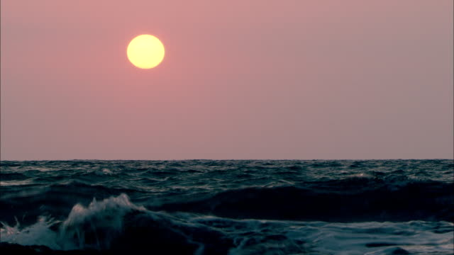 long shot static - a purple sky and pale sun glow above crashing waves. / uk - seascape stock videos & royalty-free footage