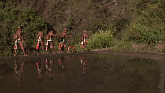 Long Shot static - A warrior hunting party walks in a line around a mountain lake. / Philippines