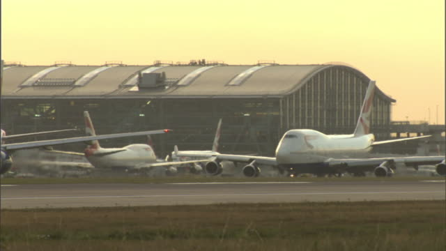 Long Shot static - Airplanes queue on a runway. / London, England
