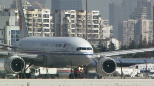 Long Shot static - An Air China passenger jet turns on a tarmac./Shanghai, China