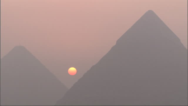 Long Shot, static  - An orange sun glows through the smog between the Great Pyramids of Giza / Egypt