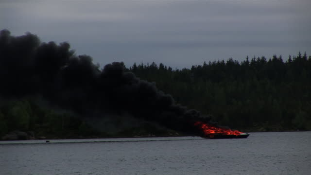 long shot static - black smoke billows from a burning boat on a lake.  - anchored stock videos & royalty-free footage