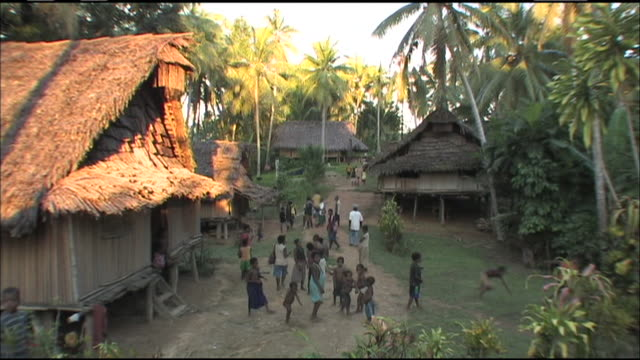 long shot static - children play in a village in papua new guinea. / papua new guinea - papua stock videos and b-roll footage