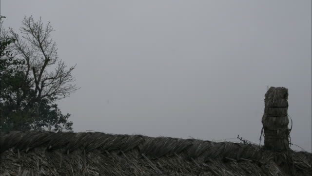 long shot static - clouds churn over a thatched roof. / india - thatched roof stock videos & royalty-free footage