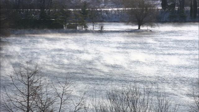 Long Shot static - Fog rises from a snowy, windswept lake. / Missouri, USA