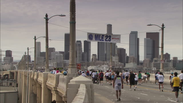 vidéos et rushes de long shot static - marathon participants jog or walk across a bridge/hollywood, california, usa - hollywood california