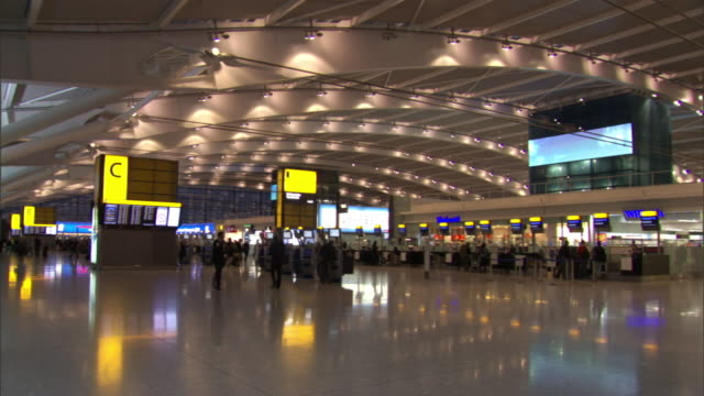 Long Shot static - Passengers check in at airport ticket counters. / London, England